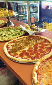 pizzas on the counter at Maggio's Pizza & Pasta